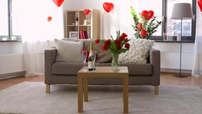 Living room or home decorated for valentines day. Valentines day, holidays and interior concept - bottle of champagne, two glasses and red flowers on table in stock video