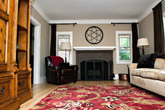 Living Room Interior. A living room interior featuring a brick fireplace, plaster walls, wood floors and furniture Royalty Free Stock Images