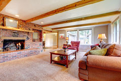 Living room interior with brick fireplace, wood beams and red. Royalty Free Stock Images