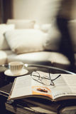 Living room Interior with coffee and book. Eyeglasses and people moving on background Stock Image