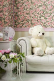 Living room interior corner with teddy bear, wall paper,clock, vases and flowers Stock Image