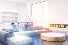 Living room interior, gray sofas, corner toned. White and gray living room interior with a round table, blue sofas and armchairs near it, tall windows and book Stock Images