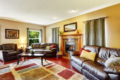 Living room interior with leather couches and fireplace Stock Image