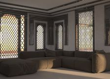 Living room interior with ornate window grills. Living room interior at street level with ornate window grills and a corner unit comfortable brown modular lounge Royalty Free Stock Images