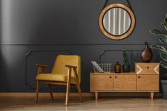 Mirror, cupboard and armchair. Living room interior with round mirror, wooden cupboard and retro armchair set on the gray wall with molding royalty free stock photos