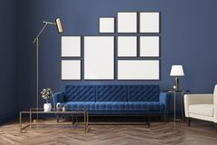 Blue living room, blue sofa, poster gallery. Living room interior with a wooden floor, loft windows, a blue sofa, a coffee table and a poster gallery on a blue Stock Image