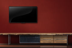 Living room led tv on red wall with wooden table modern loft sty royalty free stock photography