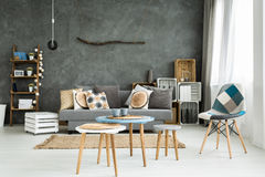 Living room in minimalistic style. Modern minimalistic and bright living room in shades of cyan with sofa full of cushions, chair, three coffee tables, carpet Stock Photos