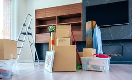 Living room with moving boxes. Large living room with stack of moving boxes stock image
