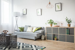 Living room with openwork table. Living room with openwork metal table, grey sofa and bookcase stock photography