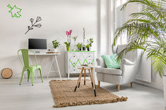 Living room with plants, commode and armchair Royalty Free Stock Image