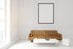 Living room with poster, brown sofa and a coffee table. Living room interior with white walls, large brown sofa, a coffee table with a jar and a white set of Stock Images