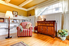 Living room with red chair and gold ceiling. stock images