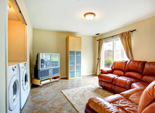 Living room with rich leather couch. Bright small living room with brown leather couch, tv and cabinet. Room has a built-in laundry area with washer and dryer royalty free stock photo
