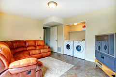 Living room with rich leather couch. Bright small living room with brown leather couch, tv and cabinet. Room has a built-in laundry area with washer and dryer royalty free stock photography