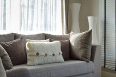 Living room with row of grey pillows on sofa. At home Stock Photos