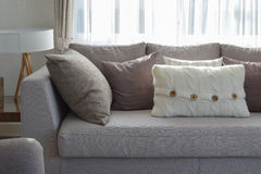 Living room with row of grey pillows on sofa. At home Stock Photo