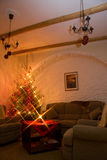 Living room and shiny christmas tree. A photo of living room furnished with big and soft couch and armchairs and a decorated natural christmas tree / fir-tree in Stock Photo
