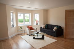 Living room in showcase home. Living room with sofa and chair on hardwood floors in showcase home in London, England Stock Images