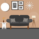 Living room with sofa small desk hanging and standing lamp brown wall dark Stock Photos