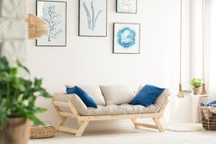 Living room with swing shelf. White living room with swing shelf, wood couch and posters stock photo
