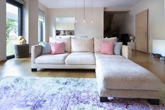 Living room with a three seater sofa with chase and four little. A living room with a three seater sofa with chaser, on a oak wooden floor royalty free stock photo