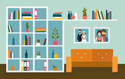 Living room wall with orange sofa and book shelves. Stock Photos