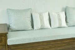 Living room with white and gray pillows on wooden sofa Stock Photos