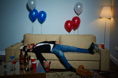 Living room after wild party. Completion of wild party: middle-aged man with beer bottle in hand sleeping on sofa, plastic cups, empty alcohol bottles and Stock Photography