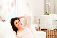 Living room with woman. Beautiful young woman sitting in living room Royalty Free Stock Photo