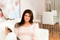 Living room with woman. Beautiful young woman sitting in living room with magazine Royalty Free Stock Photos