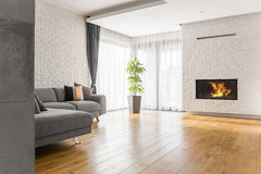 Living room with wood flooring. Fireplace and sofa Stock Images