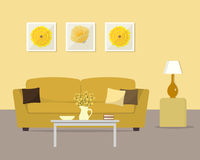 Living room in a yellow colors. There is a sofa with pillows, a table with flowers, a lamp and other objects in the image. There are also pictures in frames on Royalty Free Stock Image