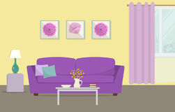 Living room in a yellow and purple colors. There is a sofa with pillows, a table with flowers, a lamp and other objects in the image. There are also pictures Royalty Free Stock Photography
