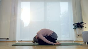 Living Room Yoga: Child`s Pose. A woman performs the child`s pose yoga position stock footage