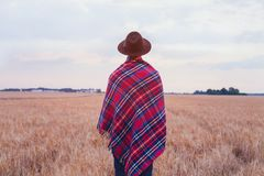 Living rural, countryside style, man in hat covered in cozy checkered plaid. Standing in the field Royalty Free Stock Photos