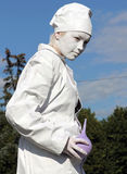 Living statue of a doctor with enema in her hands Stock Photography