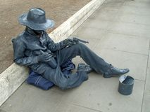 A living statue of an Italian ganster sitting, asking for handout and keeping revolvers. Rome, Italy royalty free stock image