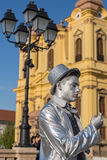 Living statue of a man silver dressed. TIMISOARA, ROMANIA - MARCH 31, 2017: Living statue of a man, silver dressed and present on the street inside the CheckART Royalty Free Stock Photo