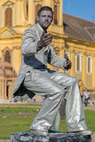 Living statue of a man, silver dressed. TIMISOARA, ROMANIA - APRIL 1, 2017: Living statue of a man, silver dressed and present on the street inside the CheckART Royalty Free Stock Image
