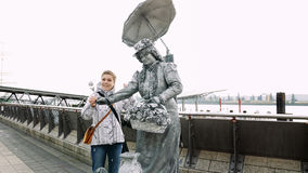 Living statue poses with tourist passerby Royalty Free Stock Photos