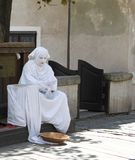Street Performer Resting between Acts. A living-statue street performer resting between acts Royalty Free Stock Photography