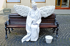 Living statue - a white angel sitting on a bench Royalty Free Stock Photos