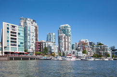 Living in Vancouver. False Creek, a short inlet in the heart of Vancouver, British Columbia, Canada is bordered by tall luxurious condo buildings and their Royalty Free Stock Image
