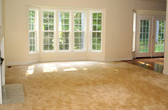 Livingroom Interior. Interior of newer home with bay windows allowing the sunlight through Stock Photo