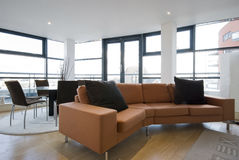 Livingroom with large orange sofa. And floor to ceiling windows stock photo