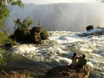 Livingston Falls in Zambia Africa. A view on the edge of Livingston Falls in Zambia Africa with water spray and rocks plus a male and female sitting on a rock Stock Image