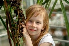 Portrait, little girl seven years, sitting next palm tree stock photos