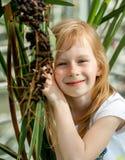 Portrait, little girl seven years, sitting next palm tree stock photo
