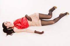Livlös brunett som ligger på golvet arkivbild